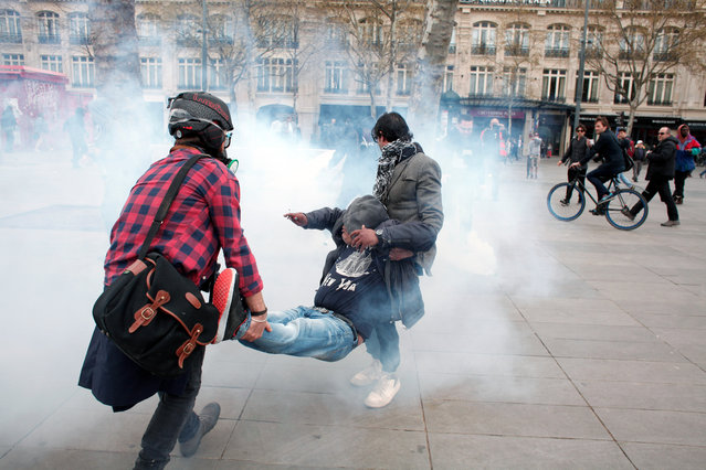 Demonstrators carry an injuried man during a high school protest in Paris, Thursday, April 14, 2016. (Photo by Christophe Ena/AP Photo)