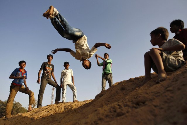 A boy from a local dance group practices a somersault in a slum area in the western Indian city of Ahmedabad March 19, 2014. (Photo by Amit Dave/Reuters)