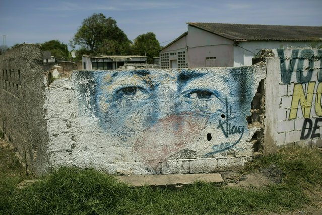 An eroded mural of Venezuela's late President Hugo Chavez covers a wall in Machurucuto, Venezuela, Sunday, May 5, 2019. For many town residents, their only contact with the Cubans is at a hospital in a nearby city where Cuban doctors treat them for free, albeit with alarmingly scant medical supplies. (Photo by Rodrigo Abd/AP Photo)