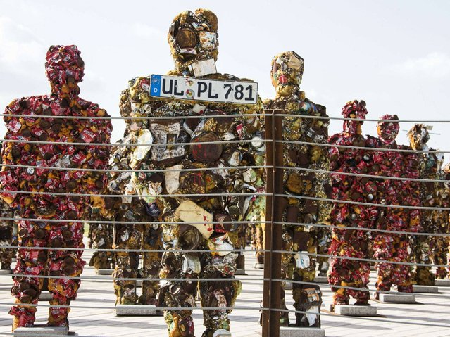 """""""Trash People"""" constructed from 20 tons of recycled material, include even the license plate. (Photo by Jack Guez/AFP Photo)"""