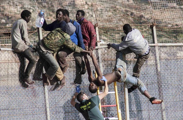 An African migrant is lowered down from a border fence by a Spanish Civil Guard as fellow migrants assist, at the border between Morocco and Spain's north African enclave of Melilla during the latest attempt to cross into Spanish territory, April 3, 2014. Spain has more than doubled the strength of security forces at Melilla, after about 500 people stormed its fences in the biggest border rush for years earlier this month. (Photo by Jesus Blasco de Avellaneda/Reuters)