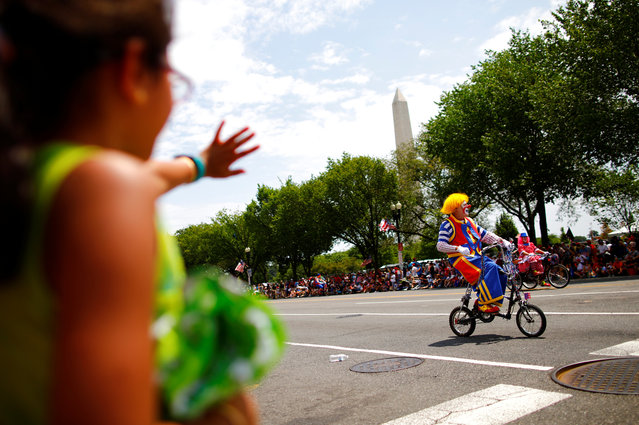 A clown passes by on a bicycle as he takes part in a parade during Fourth of July Independence Day celebrations in Washington, D.C., U.S., July 4, 2019. (Photo by Carlos Barria/Reuters)
