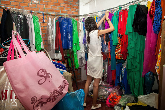 Sun Model assistant Miss Voleak chooses clothes for the models to wear during training on March 31, 2014 in Phnom Penh, Cambodia. (Photo by Omar Havana/Getty Images)