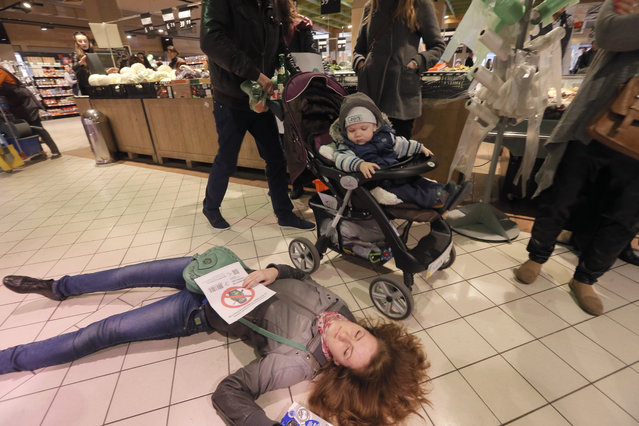 A consumer passes by Ukrainians laying on a store's floor as dead bodies in a flash mob action protesting against buying of the Russian goods in Kiev, Ukraine, Saturday, April 5, 2014. Following Russia's annexation of Ukraine's Crimean peninsula, the diplomatic strain between Ukraine and Russia is now turning into a trade war. (Photo by Efrem Lukatsky/AP Photo)