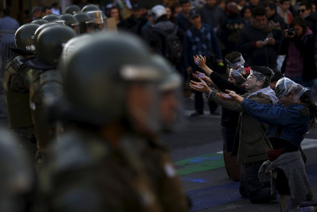 Students perform next to riot policemen during a demonstration to demand changes in the Chilean education system in Santiago, Chile June 25, 2015. (Photo by Ricardo Moraes/Reuters)