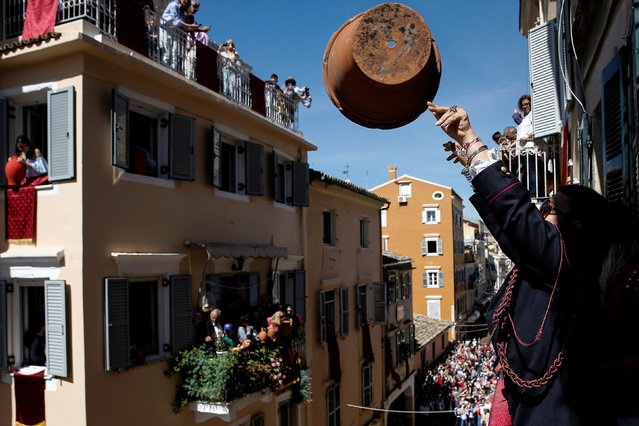 "A woman throws a clay pot from a balcony during the Greek Orthodox Easter tradition of ""Botides"" on Holy Saturday marking the so-called ""First Resurrection"", on the island of Corfu, Greece, April 30, 2016. (Photo by Alkis Konstantinidis/Reuters)"