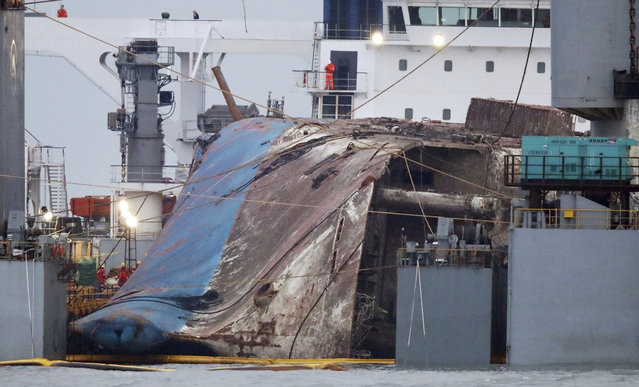 The sunken Sewol ferry is loaded onto a semi-submersible transport vessel during the salvage operation in waters off Jindo, South Korea, Saturday, March 25, 2017. Salvage crews towed the corroded 6,800-ton South Korean ferry toward a transport vessel on Friday after it was successfully raised from waters off the country's southwest coast. The massive attempt to bring the ferry back to shore, nearly three years after it sank, killing 304 people, is being closely watched by a nation that still vividly remembers the horrific accident. (Photo by Lee Jin-wook/Yonhap via AP Photo)