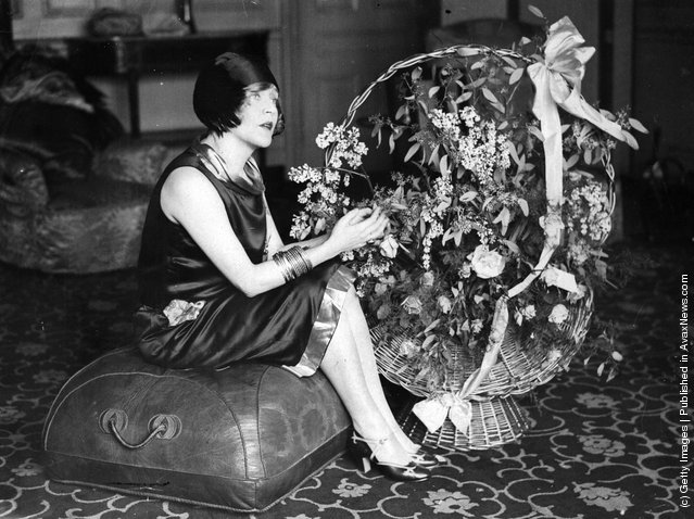 1925: American film star, Mae Murray (1889 - 1965) seated on a pouffe with a large basket of flowers