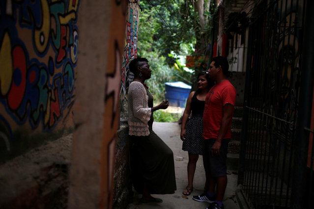 Solange, a worker at Pousada Favelinha hostel, talks to guests outside the hostel in Pereira da Silva favela, in Rio de Janeiro, Brazil, April 29, 2016. (Photo by Pilar Olivares/Reuters)