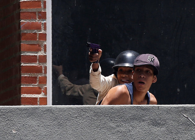 A youth aiming a toy gun, reacts during clashes with security forces during an opposition rally in Caracas, Venezuela on April 4, 2017. (Photo by Carlos Garcia Rawlins/Reuters)
