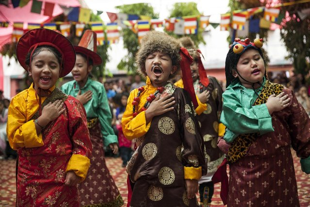 Exiled Tibetan school children wearing traditional costumes sing at a gathering to celebrate their spiritual leader's 80th birthday in New Delhi, India, Monday, July 6, 2015. (Photo by Tsering Topgyal/AP Photo)