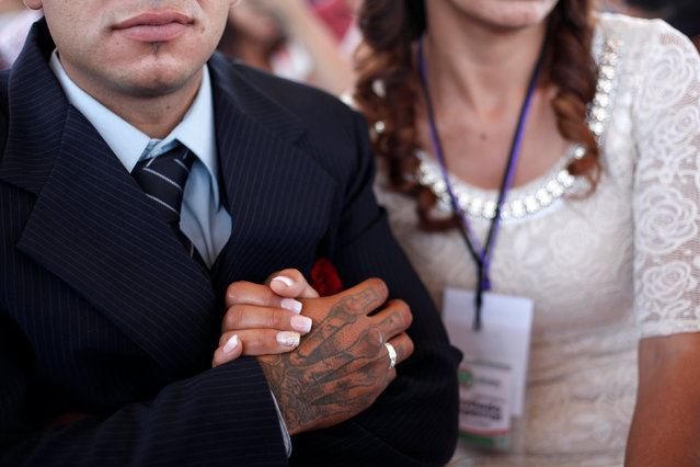 An inmate holds hands with his fiancee during a mass wedding ceremony at the state prison in Ciudad Juarez, Mexico, May 6, 2016. (Photo by Jose Luis Gonzalez/Reuters)