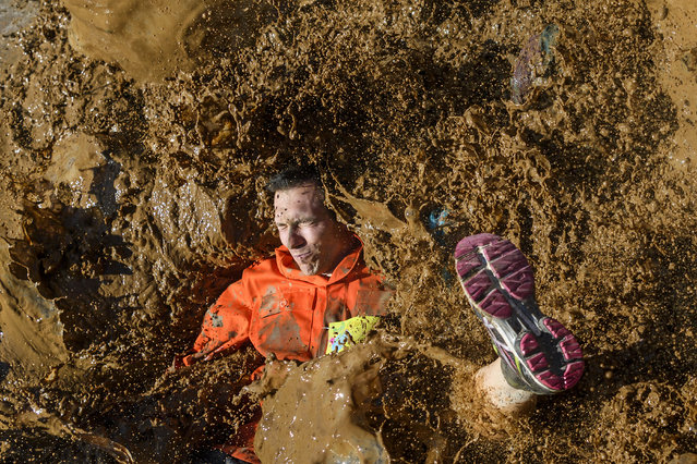 """A competitors lands in mud as they take part in the """"Barjot Run"""" obstacle race in Biere, western Switzerland, on April 8, 2017. Some 1500 participants took part in the 7.5km-long race. (Photo by Fabrice Coffrini/AFP Photo)"""