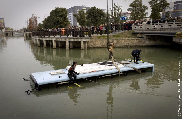 Workers prepare to salvage a bus on December 29, 2011 in Suzhou, China. A bus carrying eight people collided with a car on a bridge and crashed into river on Thursday afternoon, injuring all aboard