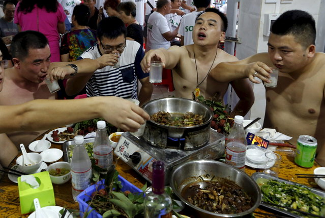 People toast over a dog meat dish at a dog meat restaurant in Yulin, Guangxi Autonomous Region, June 22, 2015. (Photo by Kim Kyung-Hoon/Reuters)