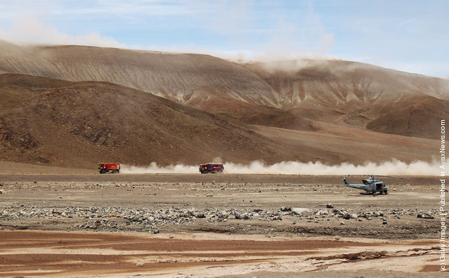 Trucks race across a valley floor during stage eight of the 2012 Dakar Rally from Copiapo to Antofagasta