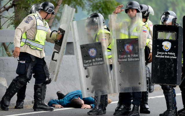 An injured man lies on the street next to national guard members during a demonstration in Caracas on May 11, 2016. With helmets, shields and bulletproof, military and Venezuelan police vests prevented Wednesday the advance of thousands of opponents who tried to reach the headquarters of the National Electoral Council (CNE), to demand accelerate the process of a recall referendum against President Nicolas Maduro. (Photo by Federico Parra/AFP Photo)