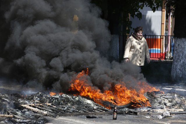 A woman walks past a burning barricade near the city hall in Mariupol, on May 10, 2014. (Photo by Marko Djurica/Reuters)