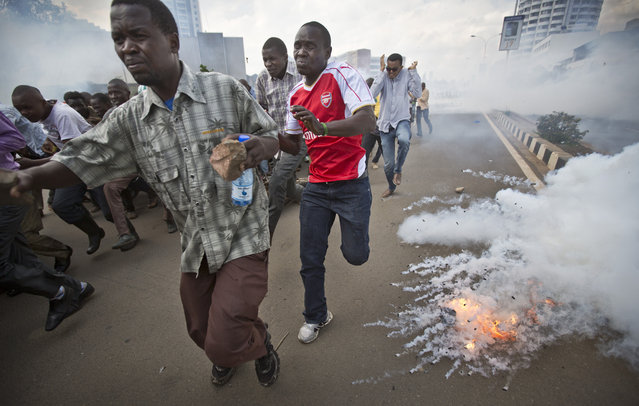 Opposition supporters, some carrying rocks, flee from exploding tear gas grenades fired by riot police, during a protest in downtown Nairobi, Kenya Monday, May 16, 2016. (Photo by Ben Curtis/AP Photo)