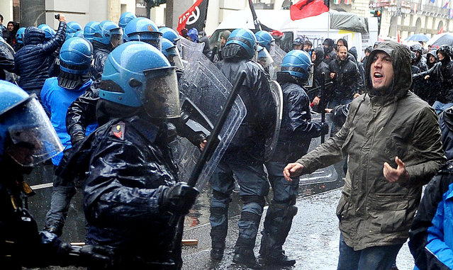 Protesters clash with riot police as they attempt to force their way closer to a Labor Day march, in Turin, Italy, Monday, May 1, 2017. (Photo by Alessandro Di Marco/ANSA via AP Photo)