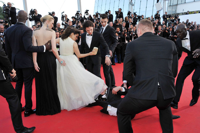 "A man invades the Red Carpet and is held by security at the ""How To Train Your Dragon 2"" Premiere at the 67th Annual Cannes Film Festival on May 16, 2014 in Cannes, France. The man stuck his head up America`s skirt before being dragged away by security. Pictured: Djimon Hounsou, Cate Blanchett, America Ferrera and Kit Harington. (Photo by Camilla Morandi/IPA)"