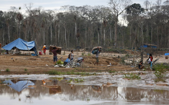 Miners and their families leave a camp after a Peruvian police operation to destroy illegal gold mining camps in a zone known as Mega 14, in the southern Amazon region of Madre de Dios July 14, 2015. (Photo by Janine Costa/Reuters)