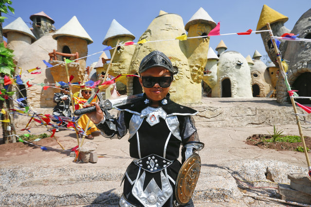 """""""Dwarf Empire"""" cast member Lv Qiangyong poses backstage in front of the fairy tale-like village after his performance at the Dwarf Empire theme park outside Kunming, China's Yunnan province, 04 April 2013. (Photo by Diego Azubel/EPA)"""