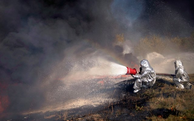 Ukrainian rescuers extinguish a fire on a lake as part of their psychological training during a drills near the Boryslav city, some 70 km from Western-Ukrainian city of Lviv, 16 October 2019. (Photo by Ukrinform/Barcroft Media)