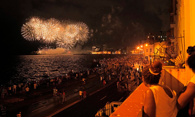 Cubans gather at Havanas Malecon waterfront to watch the fireworks on the eve of the city's 500th anniversary on November 15, 2019, in Havana, Cuba. The fireworks were launched from the opposite side of the Havana bay, at the El Morro fortress and lighthouse complex. (Photo by Sven Creutzmann/Mambo photo/Getty Images)