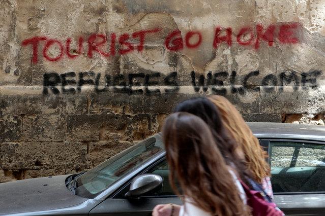 People walk past a graffiti in Palma de Mallorca, in the Spanish island of Mallorca, May 23, 2016. (Photo by Enrique Calvo/Reuters)