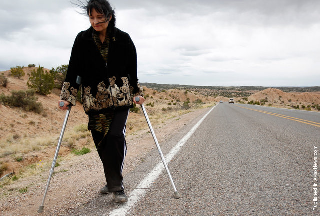 Bernadette Saavedre walks along the side of the road as she makes her pilgrimage to El Santuario de Chimayo in Chimayo, New Mexico April 23, 2011. Thousands of people walk to the little chapel over Easter weekend, where they believe the dirt inside holds the power to heal, some from as far away as Mexico and Colorado