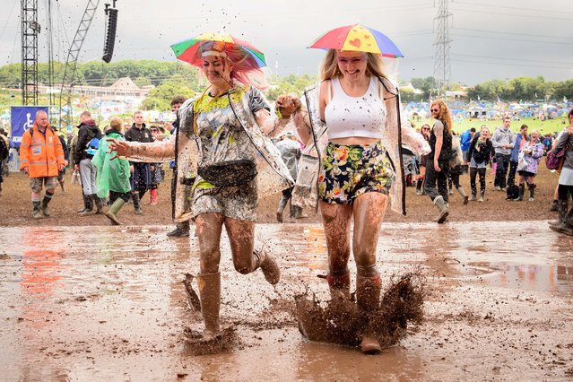 Revellers run through a puddle as they pose for photographers, on the first official day of the Glastonbury Festival of Music and Performing Arts on Worthy Farm in Somerset, south west England, on June 27, 2014. (Photo by Leon Neal/AFP Photo)