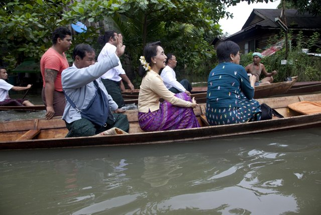 Myanmar opposition leader Aung San Suu Kyi, center, rides a boat on her way to a monastery where flood victims are sheltered, Monday, August 3, 2015, in Bago, 80 kilometers (50 miles) northeast of Yangon, Myanmar. (Photo by hin Maung Win/AP Photo/)