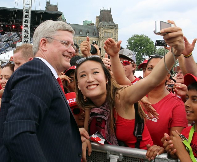 Prime Minister Stephen Harper smiles as has his picture taken with a Canada Day celebrant on Parliament Hill in Ottawa, Tuesday July 1, 2014. (Photo by Fred Chartrand/The Canadian Press)