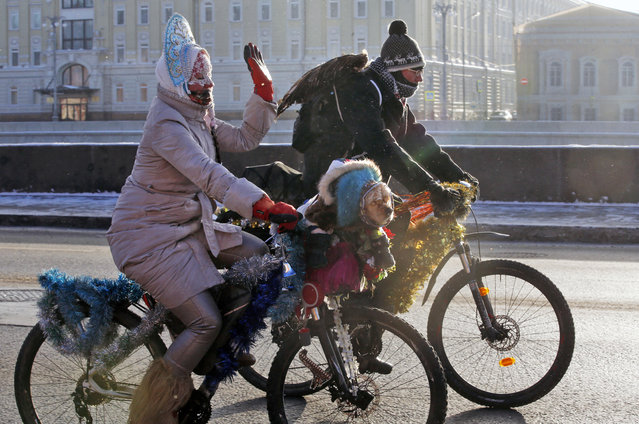 Wrapped in warm clothes a cyclist has her pet dog accompanying her during a winter bike parade in Moscow, Russia, 08 January 2017. Russians enjoy the Julian calendar Orthodox Christmas holidays despite extreme frost temperatures of down to minus 25 degrees Celsius. (Photo by Sergei Chirikov/EPA)