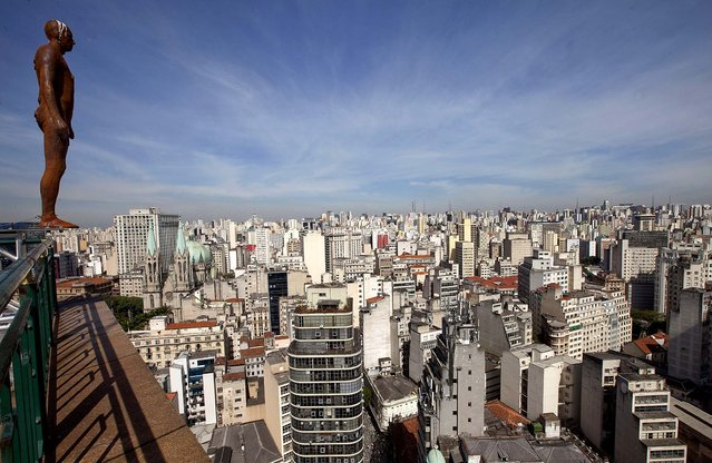 A sculpture by British artist Antony Gormley is displayed on the edge of a building in downtown Sao Paulo on May 11, 2012