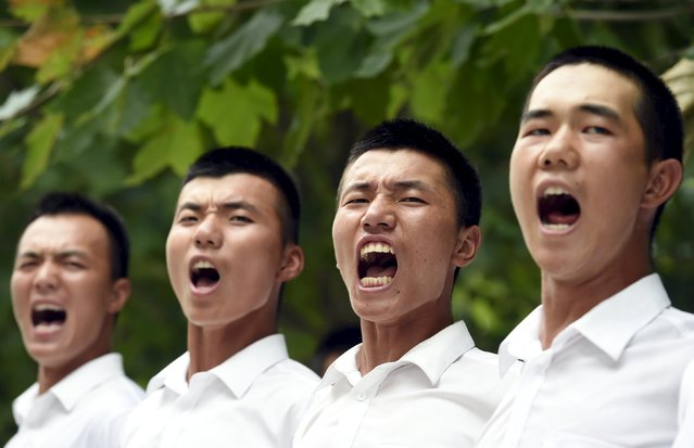 Paramilitary policemen and members of a gun salute team shout slogans as they stand in formation during a training session for a military parade to mark the 70th anniversary of the end of the World War Two, at a military base in Beijing, China, August 1, 2015. (Photo by Reuters/Stringer)