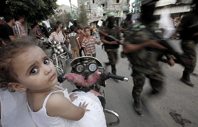 Three-year-old Nour Al Masri (L) watches as the Ezz Al-Din Al-Qassam militia, the military wing of the Hamas movement,  parades in the streets of Beit Hanun in the northern Gaza Strip, 11 August 2015. (Photo by Mohammed Saber/EPA)