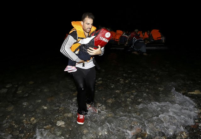A Syrian refugee carries a child as they arrive at a beach on the Greek island of Kos after crossing a part of the Aegean sea from Turkey to Greece on a dinghy August 13, 2015. (Photo by Yannis Behrakis/Reuters)