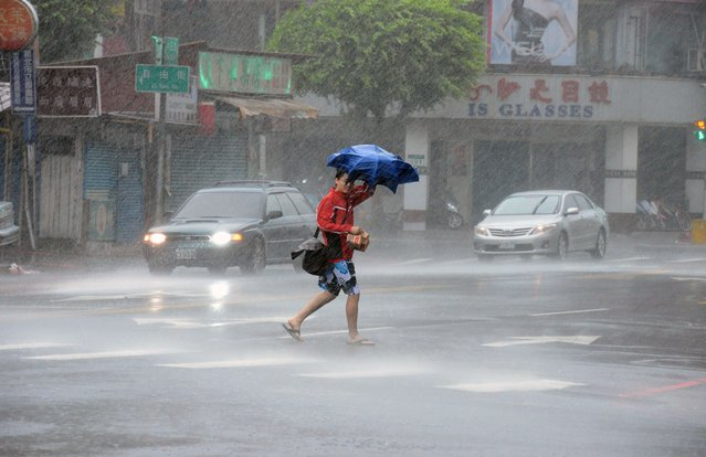 A man walks in the rain brought by Typhoon Matmo approaches Xindien district in New Taipei City on July 23, 2014. Typhoon Matmo pounded Taiwan with fierce winds and downpours, leaving five people injured, shuttering financial markets, and interrupting rail and air transportation. (Photo by Sam Yeh/AFP Photo)