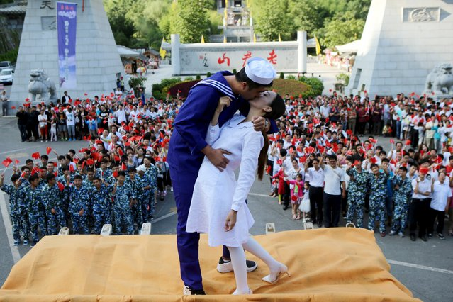 """A man and a woman dressed as a U.S. sailor and a nurse pose for photographs during an re-enactment of the famous kiss celebrating the end of World War Two in New York 70 years ago, as other participants form the figure """"70"""", to celebrate the 70th anniversary of the end of the war, in Luoyang, Henan province, China, August 15, 2015. (Photo by Reuters/Stringer)"""