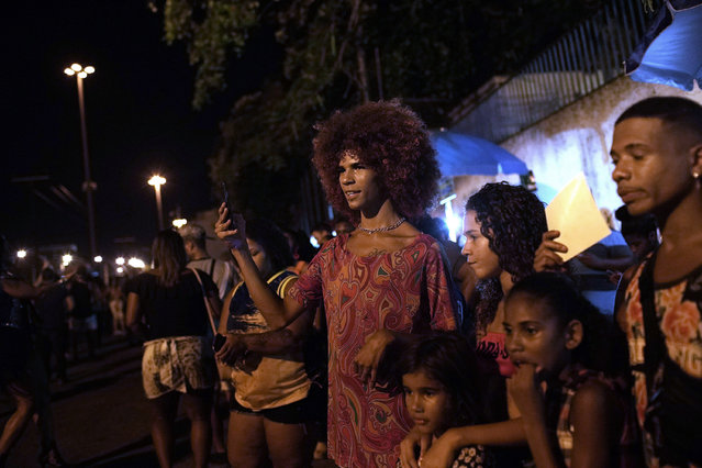 In this January 27, 2020 photo, people watch the rehearsal of the Paraiso de Tuiuti samba school in Rio de Janeiro, Brazil. Unlike dances like salsa and tango from other Latin American countries, samba has largely remained within Brazil's borders. (Photo by Silvia Izquierdo/AP Photo)