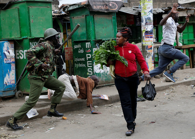 An anti riot policeman attempts to disperse people from the street as a woman carrying vegetables walks past in Mathare, in Nairobi, Kenya August 9, 2017. (Photo by Thomas Mukoya/Reuters)