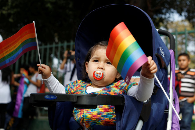 A baby holding rainbow flags attends a gay pride parade in downtown Lima, Peru on July 2, 2016. (Photo by Guadalupe Pardo/Reuters)