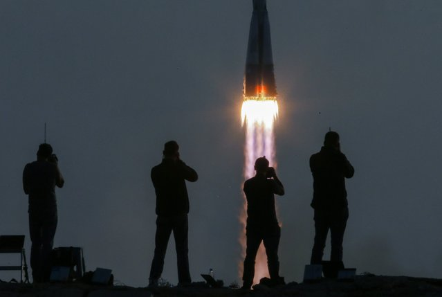 Photographers take pictures as the Russian Soyuz MS-01 spacecraft with crewmembers of the 48/49 expedition to the International Space Station (ISS), NASA astronaut Kate Rubins, cosmonaut Anatoly Ivanishin of the Russian space agency Roscosmos, and astronaut Takuya Onishi of the Japan Aerospace Exploration Agency (JAXA) aboard, lifts off from the Cosmodrome Baikonur in Kazakhstan, 07 July 2016. Rubins, Ivanishin, and Onishi will spend approximately four months on the orbital complex, returning to Earth in October. (Photo by Sergei Ilnitsky/EPA)