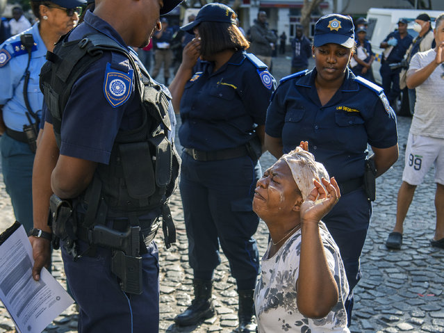 A woman reacts to a police officer outside the Central Methodist Mission Church in Cape Town, South Africa, Sunday, March 1, 2020 as city officials and police move in to evict people. Hundreds of migrants have been removed from central Cape Town by South African authorities following a months-long stand-off. The migrants removed on Sunday had demanded to be relocated to other countries claiming they had been threatened by xenophobic violence last year. (Photo by AP Photo/Stringer)