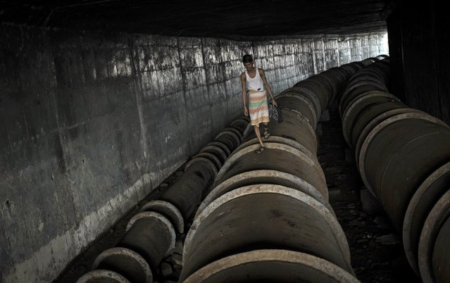 A man walks on a water pipeline used a as pathway under a bridge in Mumbai August 8, 2014. (Photo by Danish Siddiqui/Reuters)