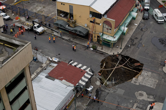 A sinkhole covers an intersection in downtown Mexico City, Thursday, August 31, 2017. An enormous sinkhole about 30 feet (10 meters) in diameter opened on the street, caused by an accumulation of water, according to civil protection. (Photo by Eduardo Verdugo/AP Photo)