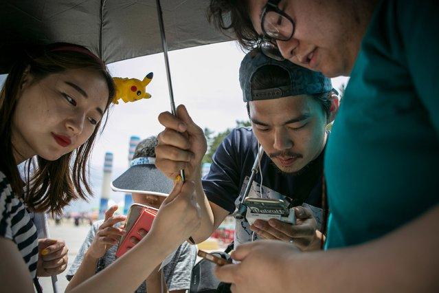 Barbie Lim (L) and Lee Jeong-hwan (C), broadcasting jockeys for Pokemon Go Korea Facebook page, look at one users mobile phone as they broadcast live on July 15, 2016 in Sokcho, South Korea. (Photo by Jean Chung/Getty Images)