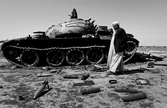 A man is seen next to a tank outside Kirkuk in 2003. Tanks had been hit by aircraft and abandoned, leaving unexploded ordnance scattered across a wide area. (Photo by Sean Sutton for the Mines Advisory Group/The Guardian)
